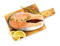 Wooden board with fresh salmon steak and lemon. On white background, top view Royalty Free Stock Photo
