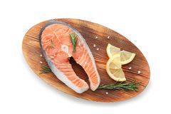 Wooden board with fresh salmon steak and lemon. On white background, top view Stock Photography