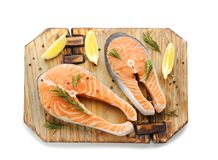 Wooden board with fresh salmon steaks and lemon. On white background, top view Royalty Free Stock Image