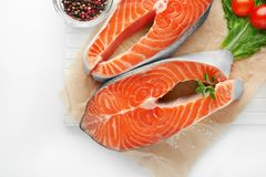 Wooden board with fresh salmon steaks. On white background Royalty Free Stock Photo
