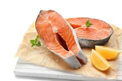 Wooden board with fresh salmon steaks. On white background Royalty Free Stock Photography