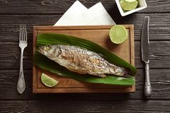 Wooden board with fried fish and green leaf. On table Royalty Free Stock Photography