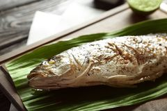 Wooden board with fried fish and green leaf. On table Stock Image