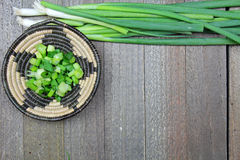 A wooden  board with green onions. A wooden board with chopped and fresh green onions with copy space Royalty Free Stock Image