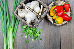 A wooden  board with green onions and peppers. A wooden board  fresh green onions and peppers with copy space Stock Photography