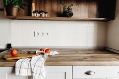 Wooden board with knife, tomatoes on modern kitchen countertop a. Nd shelf with spices and plants. cooking food. Stylish kitchen interior design in scandinavian stock photos