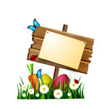 Wooden board on a loan. Egg hunt wooden board with pined blank paper on a loan with flowers eggs carrot and butterfly and ladybugs Stock Photos