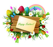 Wooden board on a loan. Happy Easter wooden board with pined paper on a loan with flowers blue butterflyes easter eggs carrots and ladybug Stock Photos
