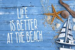 Wooden board with maritime decoration and life is better at the beach. Blue wooden board with maritime decoration and life is better at the beach royalty free stock image