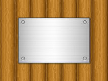 Wooden board and metal plate. Metal plate on wooden board background Royalty Free Stock Photography