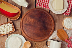 Wooden board with milk and cheese. Place for text. Healthy eating concept. View from above. Stock Photos