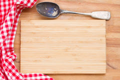 Wooden board, napkin and spoon. Empty wooden board, napkin and spoon on a table Stock Photo