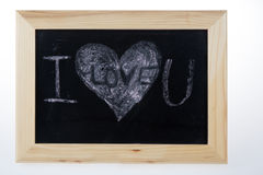 Wooden board for notes in a heart shape with the words white chalk I love you royalty free stock photo