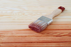 Wooden board painted with varnish. Brush laying onthe wood Royalty Free Stock Photos