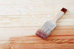 Wooden board painted with varnish. Brush laying onthe wood Royalty Free Stock Images