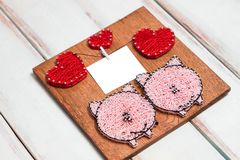 Wooden Board with pink pigs and red hearts and text frame on white wooden diagonal background. Copy space. royalty free stock image