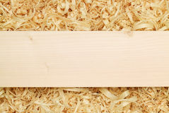 Wooden board placed on the shavings (with copyspace) Stock Photos