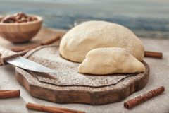 Wooden board with raw flaky dough. On table Royalty Free Stock Image