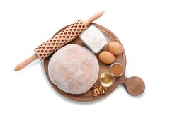 Wooden board with raw rye dough and ingredients. On white background, top view Royalty Free Stock Images
