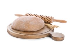 Wooden board with raw rye dough and rolling pin. On white background Royalty Free Stock Photo