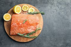 Wooden board with raw salmon and ingredients. For marinade on grey background, top view Royalty Free Stock Image