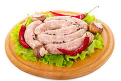Wooden board with raw sausages, mushrooms, lettuce and pepper . Wooden board with raw sausages, mushrooms, lettuce and pepper  on white background Royalty Free Stock Photography