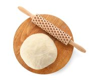 Wooden board with raw wheat dough and rolling pin. On white background, top view Stock Photo