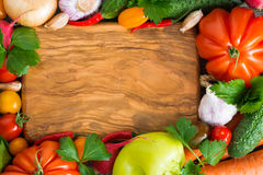 Wooden board for recipe, spices and fresh vegetables, top view Royalty Free Stock Image