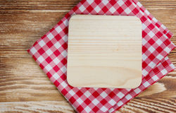 Wooden board on red cloth background. Picnic red cloth on wooden background.Empty board for recipe, copy space.Plate upper view Royalty Free Stock Photo