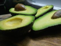 Ripe green avocado sliced in halves. On a wooden board stock photo