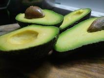Ripe green avocado sliced in halves. On a wooden board Stock Photo