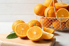 Wooden board with ripe oranges. On table royalty free stock photo