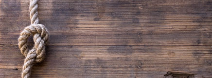 Wooden board with a rough texture and a rope Royalty Free Stock Photo