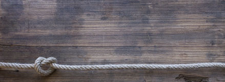 Wooden board with a rough texture and a rope. With a knot. Blank space for text Stock Photography