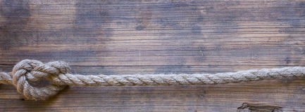Wooden board with a rough texture and a rope Royalty Free Stock Photography