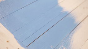 Wooden board's painting process: an artist applies blue colour with a brush stock video