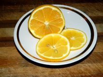 On a wooden board in a saucer of sliced lemon Stock Photos