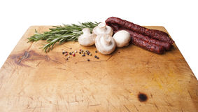 Wooden board with sausages, isolated background. Wooden cutting board with sausages. Isolated background Stock Photo