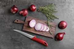 Wooden board with sliced red onion. On table, top view Royalty Free Stock Images