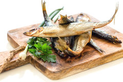 Wooden board with smoked fish, green onions and parsley close-up Stock Photo