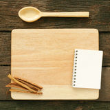Wooden board and spoon and blank earth tone note book with cinnamon Stock Image