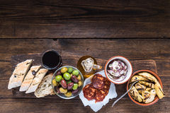 Wooden board with tapas, olives and salami and olive oil Stock Photography