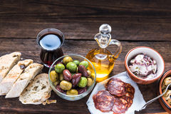 Wooden board with tapas, olives and salami and olive oil Royalty Free Stock Image