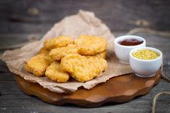 Wooden board with tasty chicken nuggets and sauces Royalty Free Stock Images