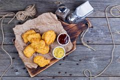 Wooden board with tasty chicken nuggets and sauces on table Stock Photos