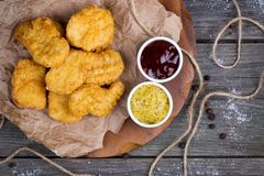 Wooden board with tasty chicken nuggets and sauces on table Royalty Free Stock Photography
