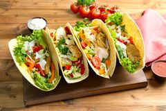 Wooden board with tasty fish tacos and sauces. On table Royalty Free Stock Images