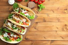 Wooden board with tasty fish tacos. On table Stock Photos