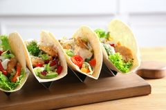 Wooden board with tasty fish tacos. On table Royalty Free Stock Image