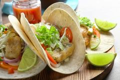 Wooden board with tasty fish tacos. On table Royalty Free Stock Photo